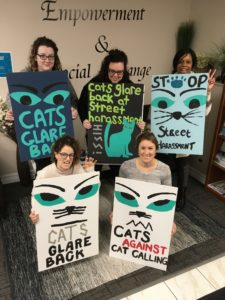 Avalon staff displaying Cats Glare Back signs from an action against street harrassment.